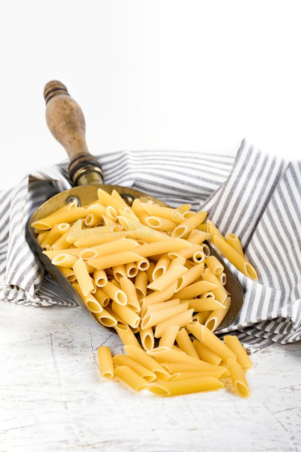 Penne Rigate Pasta. Raw pasta type penne rigate in copper bailer, on white background stock photos