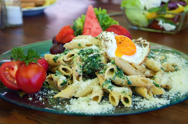 Penne with spinach. And egg with fruit and vegetable garnish stock images