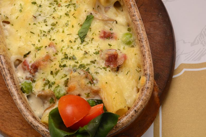 Baked pasta whit pork and cheese in ceramic pot stock image