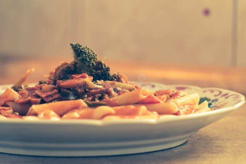 Penne z pomidorowego kumberlandu wieprzowiny panceta mashrooms i brokułami słuzyć talerz i przygotowywa umieszczającym rodzina st fotografia stock