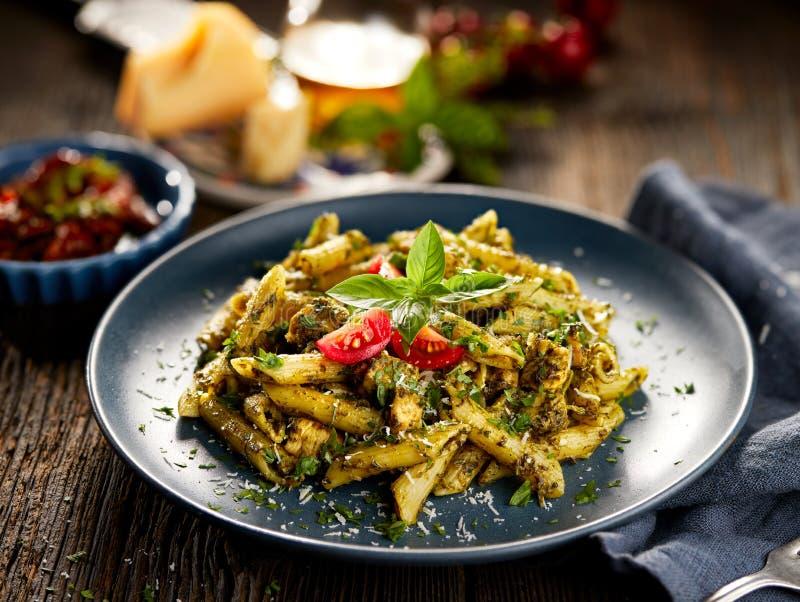 Pennedeegwaren met spinazie en kip, met parmezaanse kaaskaas en verse peterselie wordt bestrooid die stock foto