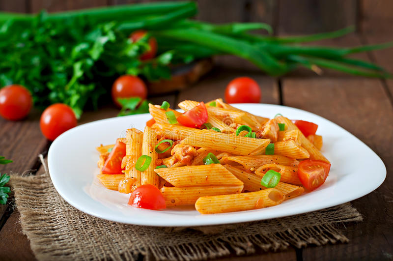 Pennedeegwaren in tomatensaus met kip, tomaten met peterselie worden verfraaid die royalty-vrije stock afbeeldingen