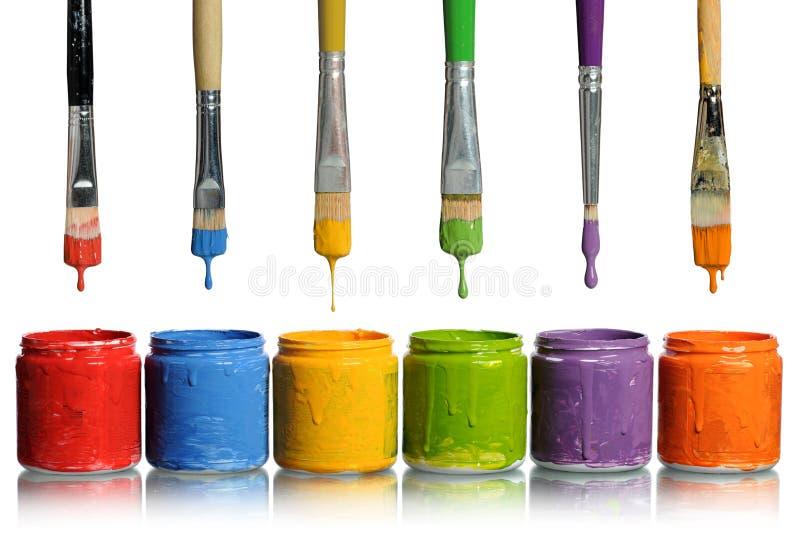 Pennelli che gocciolano nei contenitori della vernice immagini stock