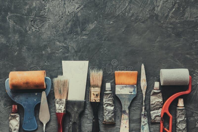 Pennelli dell'artista, rulli della spazzola, coltelli di tavolozza, primo piano dei tubi della pittura su fondo concreto grigio fotografie stock