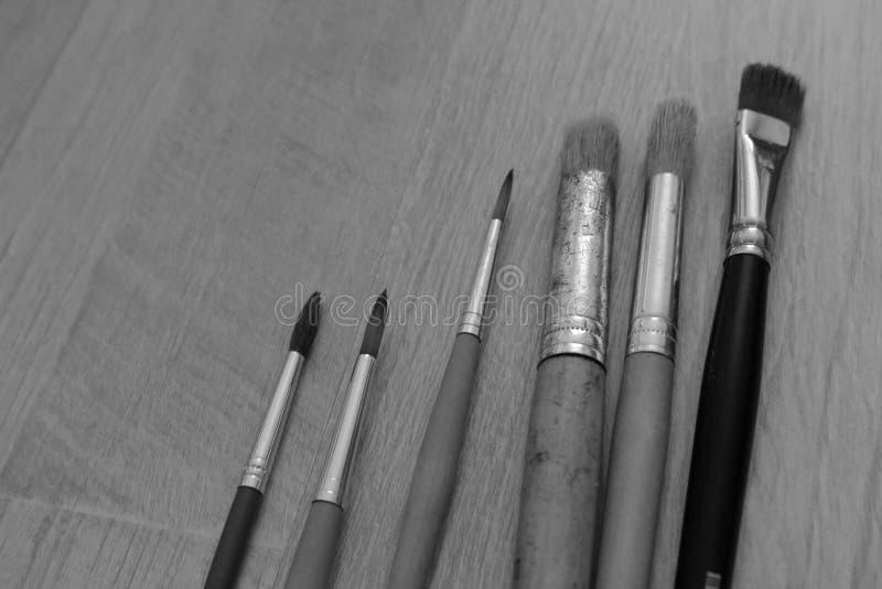 Pennelli delle dimensioni differenti su fondo di legno come monocromio in bianco e nero di concetto del disegno immagini stock