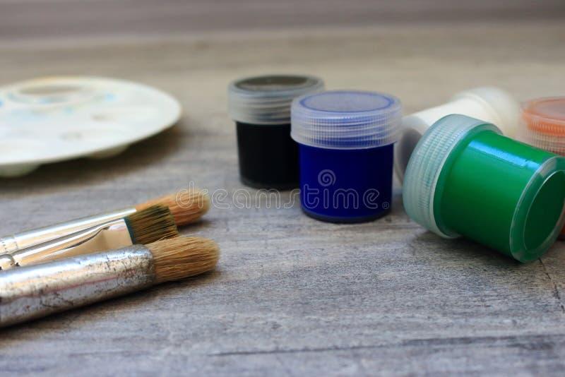Pennelli e pitture multicolori dell'acquerello e tavolozza del pallet-letto su fondo grigio come concetto del disegno immagine stock libera da diritti