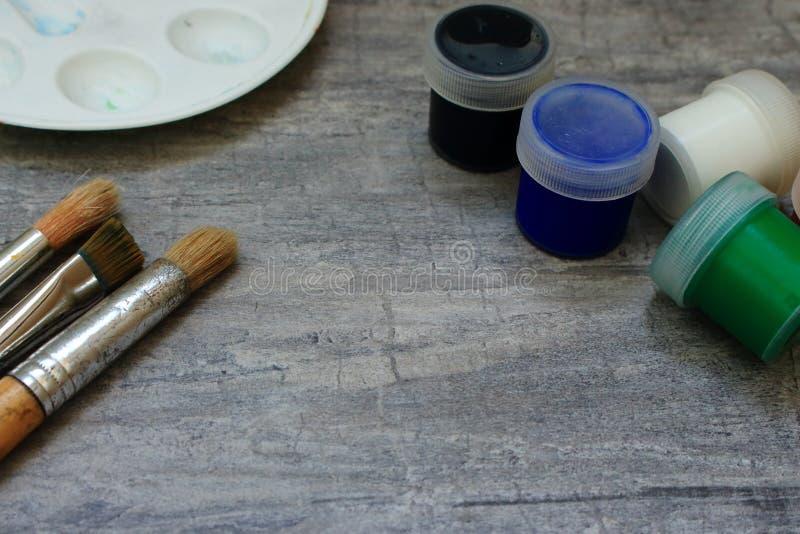 Pennelli e pitture multicolori e tavolozza dell'acquerello su fondo di pietra grigio come concetto del disegno fotografia stock libera da diritti