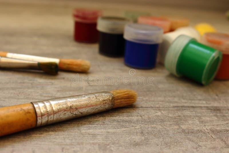 Pennelli e pitture multicolori unfocused dell'acquerello su fondo di pietra grigio come concetto del disegno immagine stock libera da diritti