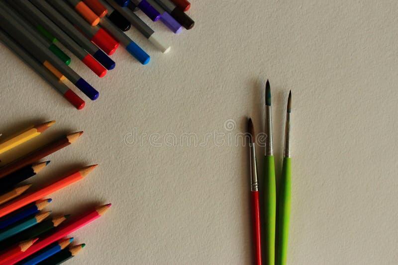 Pennelli sottili rossi e verdi e matite multicolori sul fondo del Libro Bianco come concetto del disegno fotografie stock libere da diritti