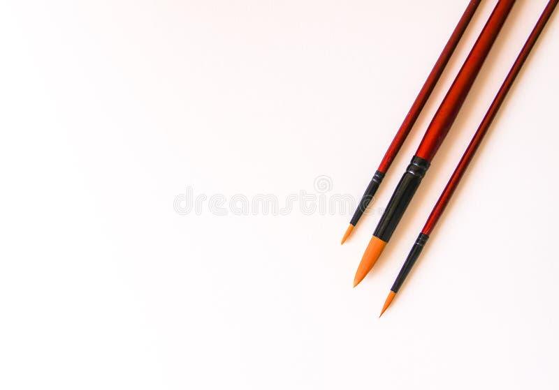 Pennelli su fondo bianco per acrilico, gouache, pittura dell'acquerello immagini stock libere da diritti