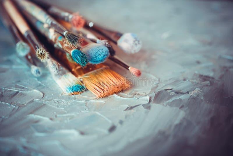 Pennelli sull'artista coperto di tela con le pitture ad olio immagini stock