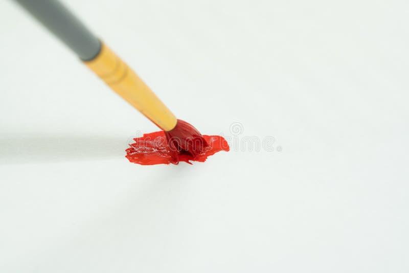 Pennello con una macchia rossa dell'olio fotografia stock