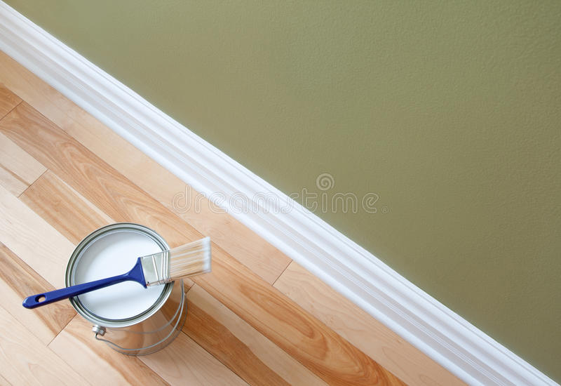 Pennello e una latta di vernice sul pavimento di legno fotografia stock