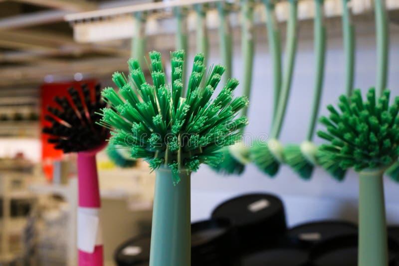 Pennello per lavastoviglie verde con spazzole sfuocate su fondo di fila nel magazzino svedese di mobili IKEA fotografia stock