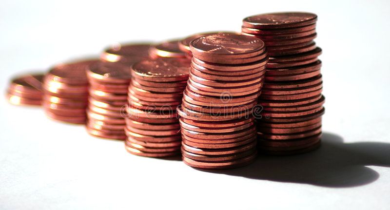 Pennies fading away. Stacks of US pennies against a white background fading away stock photo