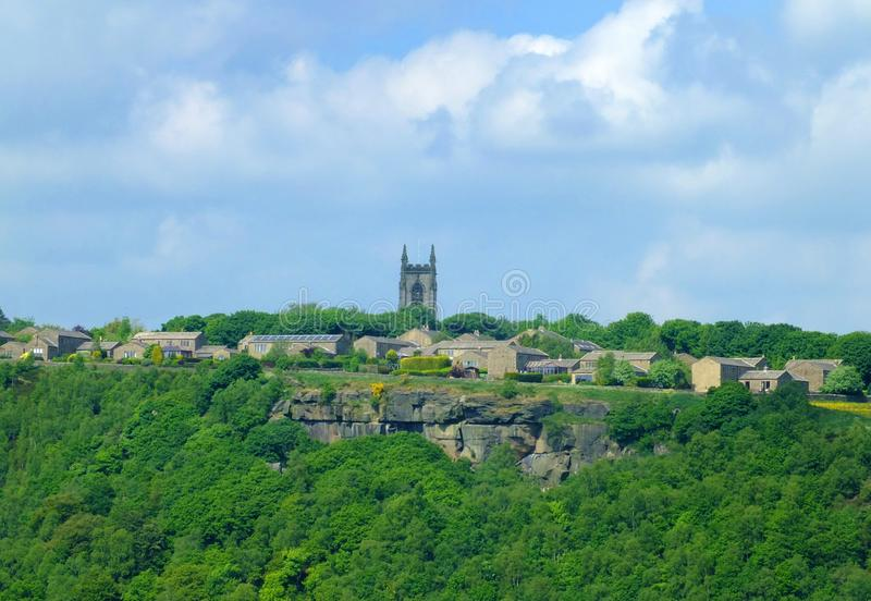The pennine village of heptonstall viewed from across the calder valley with historic church houses and surrounding woodland. And steep rocky hills royalty free stock image