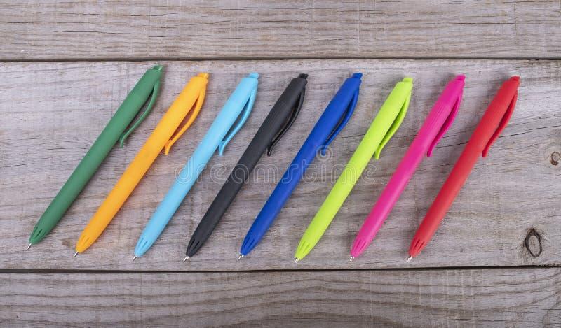 Pennor av olika färger som i rad ordnas på träbakgrund royaltyfri bild