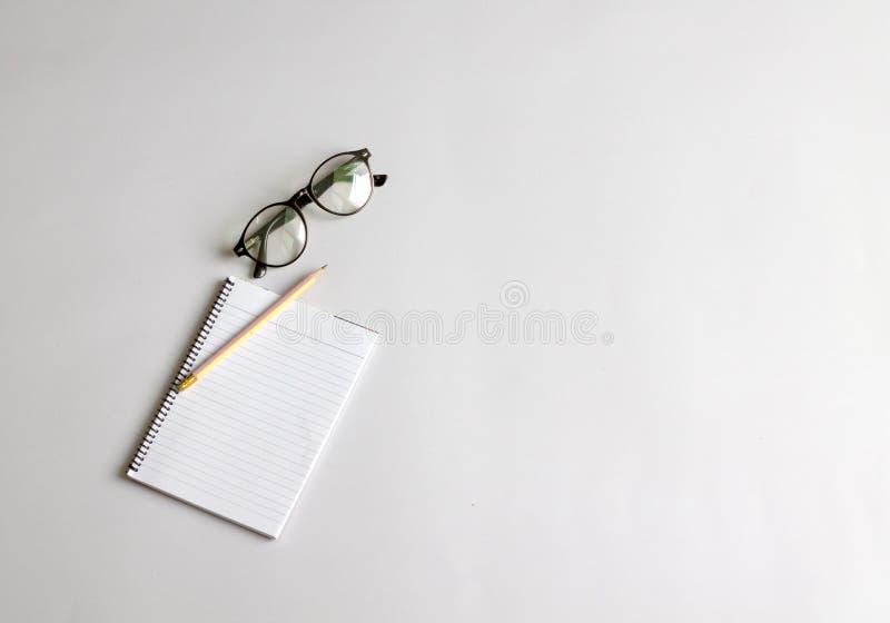 Pennor, exponeringsglas och anteckningsb?cker p? en vit bakgrund fotografering för bildbyråer