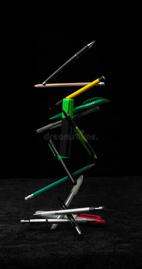 Pennor och färgstänk för blyertspennaskolavattenfall åtgärdar rörelseutbildning royaltyfri bild