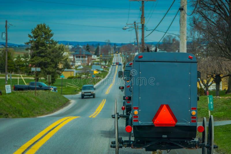 Pennsylvania, de V.S., 18 APRIL, 2018: Mening van de rug van ouderwets, Amish met fouten met een paardrijden op grint royalty-vrije stock foto