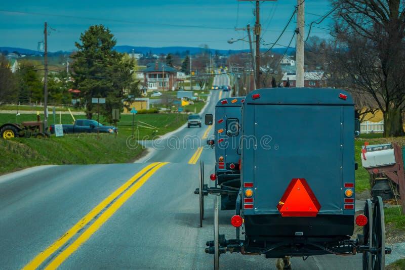 Pennsylvania, de V.S., 18 APRIL, 2018: Mening van de rug van ouderwets, Amish met fouten met een paardrijden op grint stock foto's