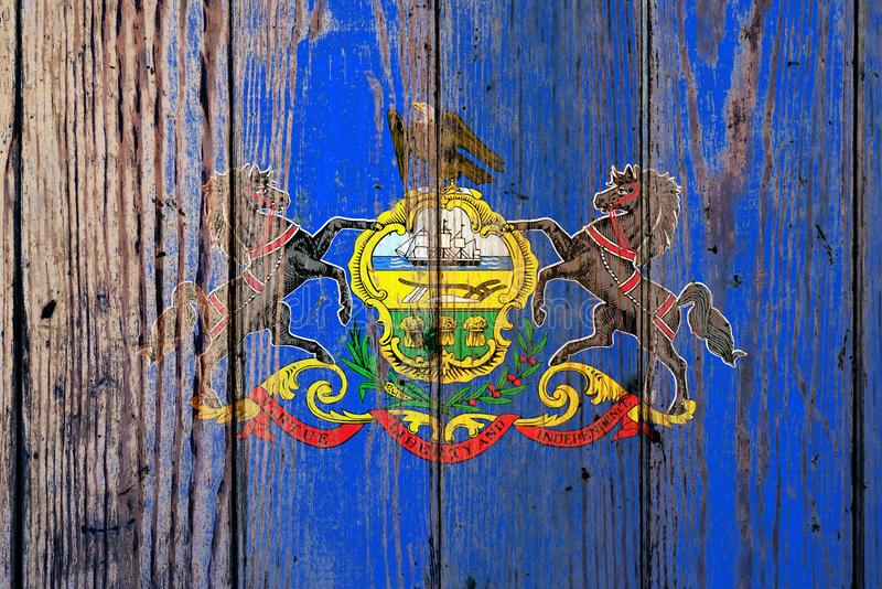 Pennsylvania US state national flag on a gray wooden boards background on the day of independence in different colors of blue red. And yellow. Political and stock image