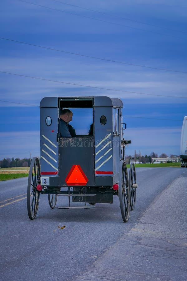 Pennsylwania, usa, KWIECIEŃ, 18, 2018: Plenerowy widok plecy powozik z ludźmi inside i a staromodni, Amish, fotografia royalty free