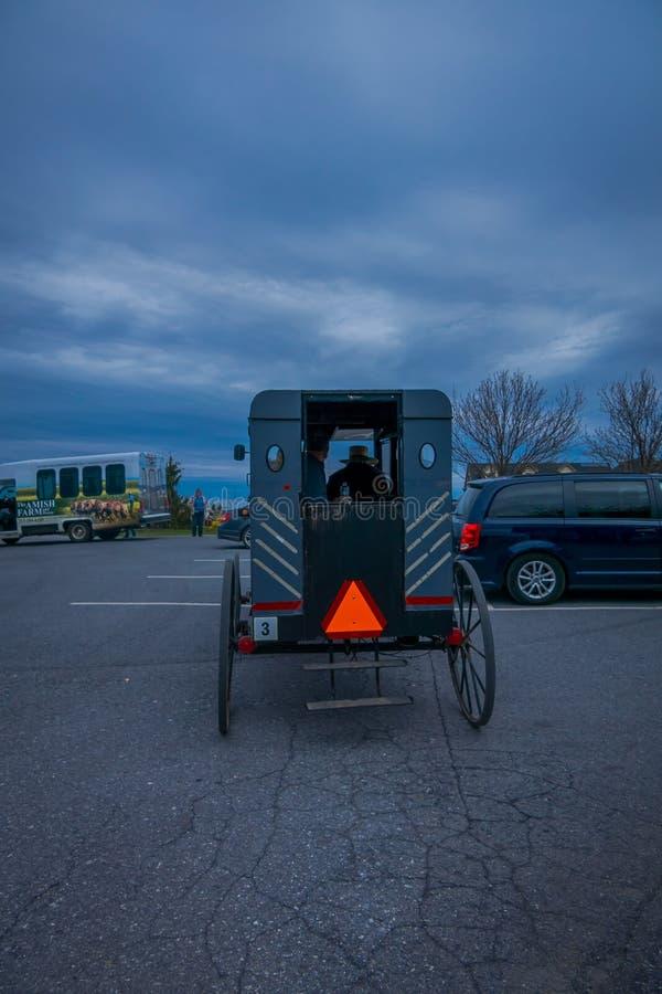 Pennsylwania, usa, KWIECIEŃ, 18, 2018: Plenerowy widok plecy powozik z ludźmi inside i a staromodni, Amish, zdjęcie stock