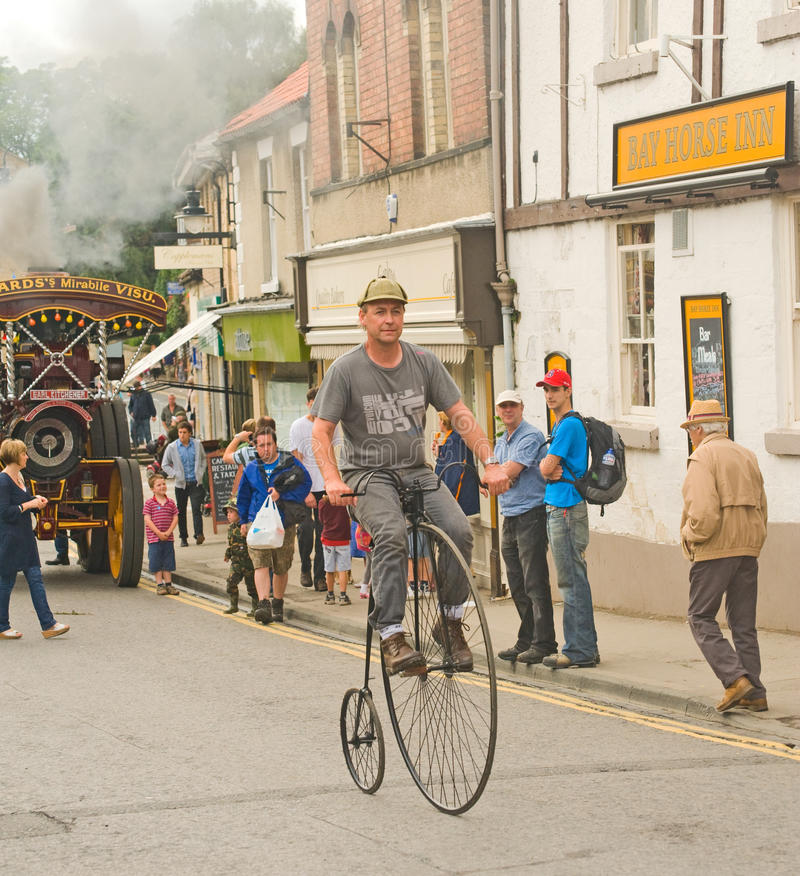 Penny farthing bicycle being ridden.