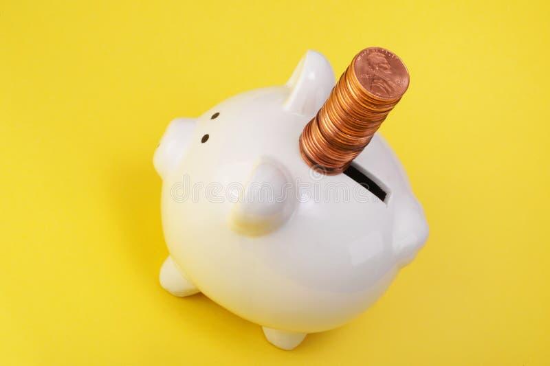 Pennys für die piggy Querneigung lizenzfreie stockfotos