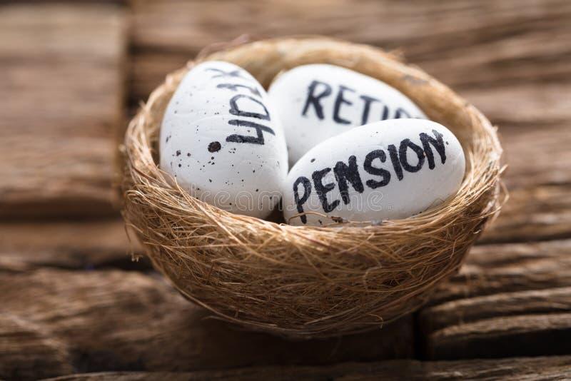 A pensão 401K e aposenta-se escrito nos ovos brancos no ninho imagem de stock royalty free