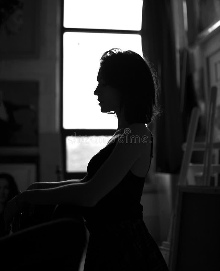 Pensée se reposante de jeune belle fille de hippie dans les sous-vêtements sexy dans le studio d'artiste près de la fenêtre noire photographie stock