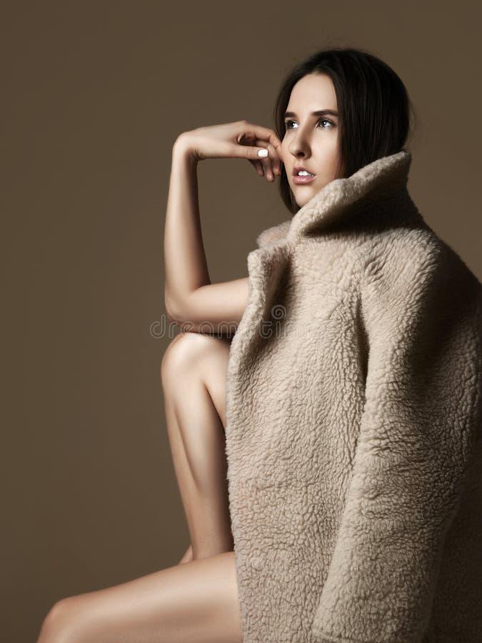 Pensée se reposante de jeune belle fille de hippie sexy dans le manteau de fourrure gris-clair de ressort nu photos stock