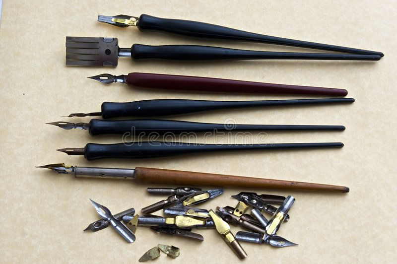 Pens. Collection of drawing and writing pens with extra nibs on parchment paper background stock photography