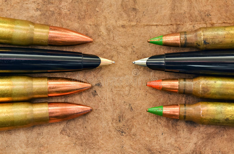 Pens and bullets. Symbolic expression of preference for peace and not war royalty free stock photography