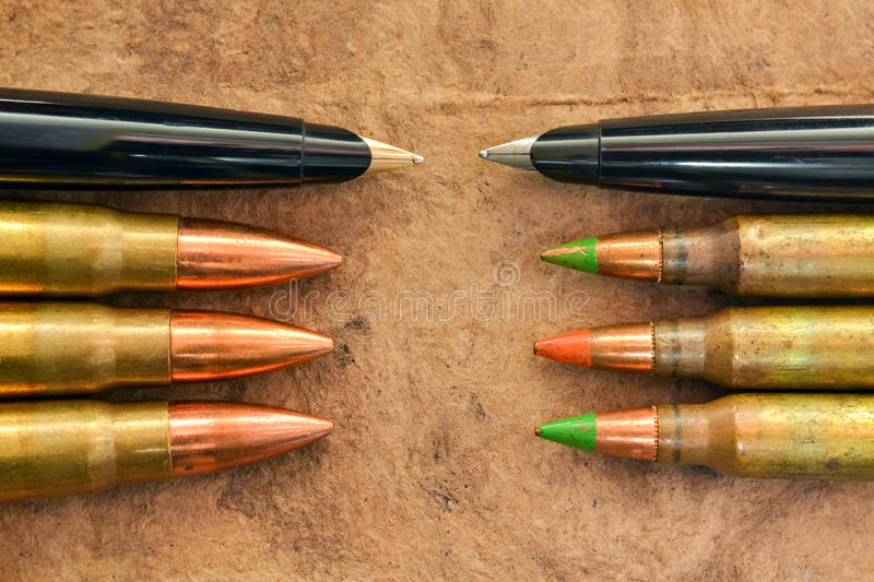 Pens and bullets. Symbolic expression of preference for peace and not war royalty free stock photo
