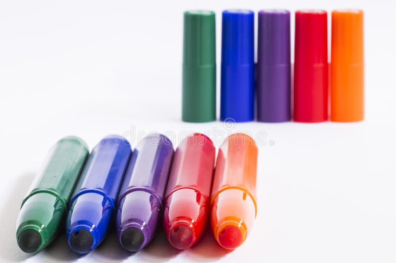 Pens. Colored pens and their colored caps stock photo