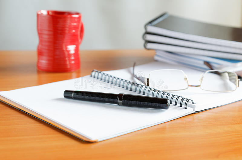Pens with a cup of coffee. And organizers royalty free stock image