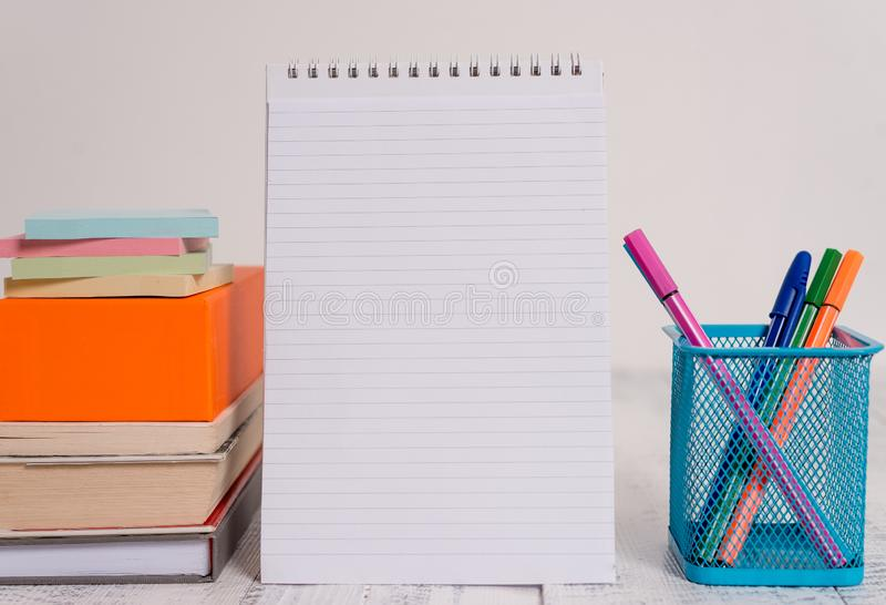 Pens metal holder blank colored stacked note pads books square box spiral lying retro vintage rustic old table royalty free stock images