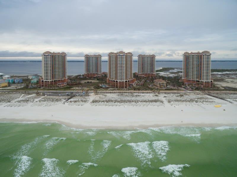 PENSACOLA, ФЛОРИДА - 13-ОЕ АПРЕЛЯ 2016: Мексиканский залив и здания островного курорта Portofino с песчаным пляжем в Pensacola стоковое изображение rf