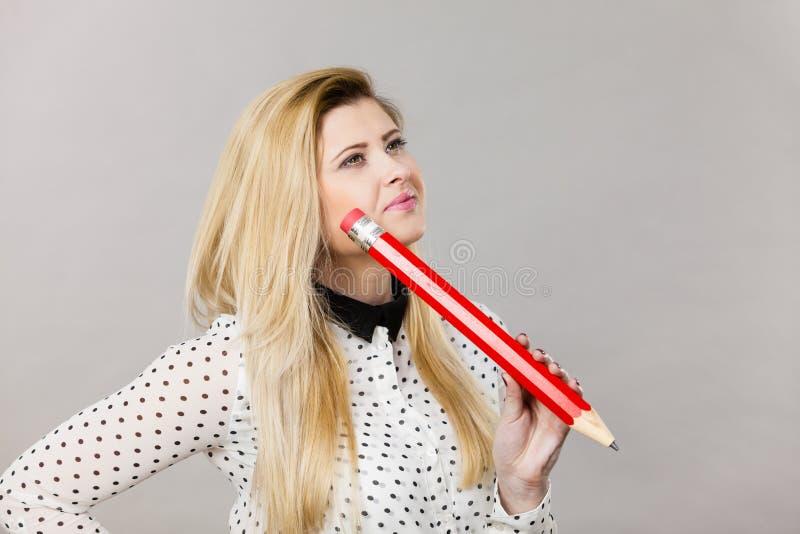 Pensamento confundido mulher, lápis grande à disposição fotografia de stock royalty free