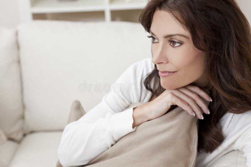 Pensamento de assento da mulher triguenha em casa no sofá foto de stock