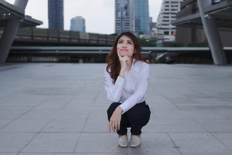 Pensamento e conceito pensativo do negócio Retrato da mulher de negócios asiática nova atrativa que olham segura e do sorriso em  fotos de stock royalty free
