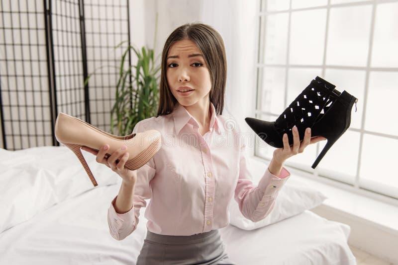 Pensamento fêmea novo pensativo sobre sapatas foto de stock royalty free