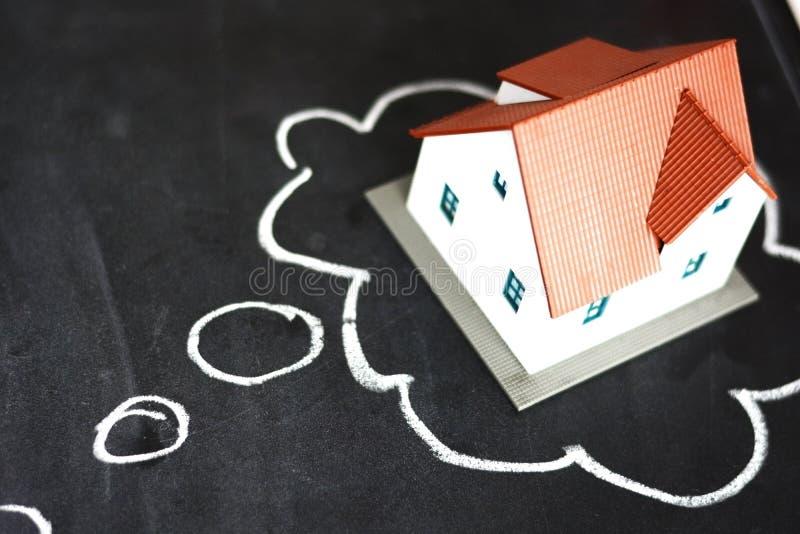 Pensamento para comprar uma casa nova com a casa do esboço e do modelo pequeno no quadro-negro fotografia de stock