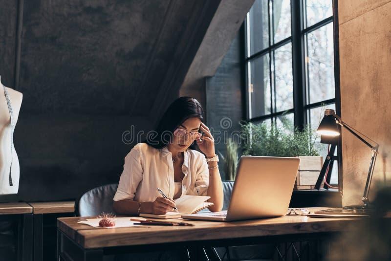 Pensamento sobre cada detalhe Jovem mulher concentrada que toma não fotos de stock