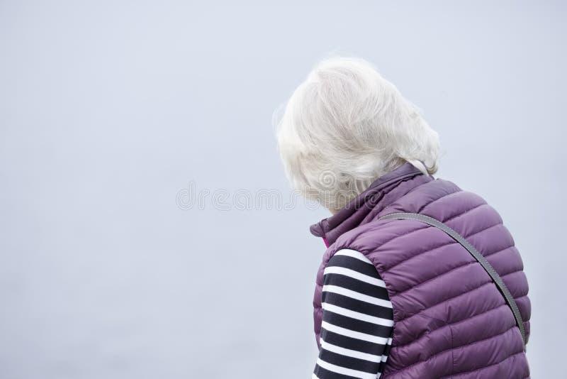 Pensamiento mayor mayor de la señora triste y solo contra el cielo claro en blanco del fondo fotografía de archivo