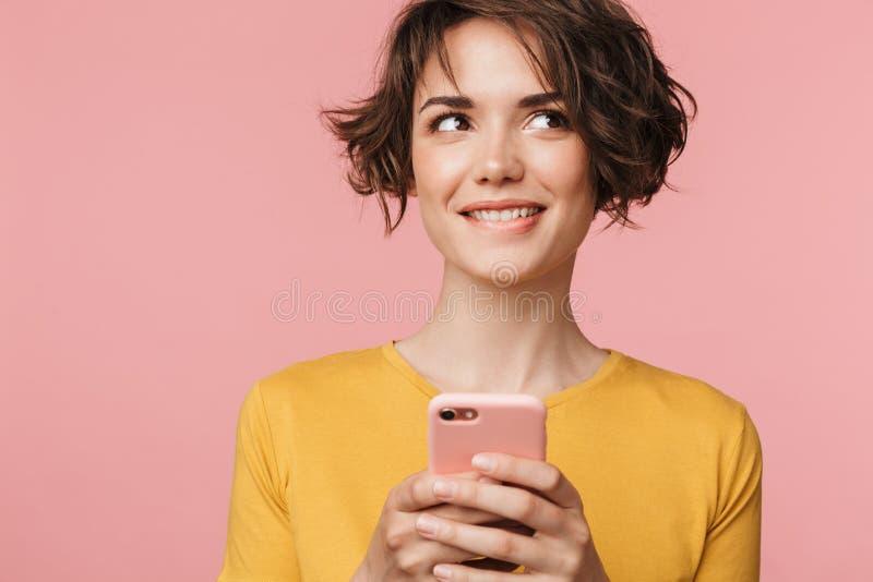 Pensamiento soñando la presentación hermosa joven de la mujer aislada sobre fondo rosado de la pared usando el teléfono móvil imagenes de archivo