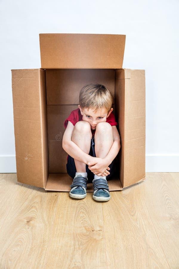 Pensamiento triste del niño hunched en una caja, lejos de la timidez fotografía de archivo libre de regalías