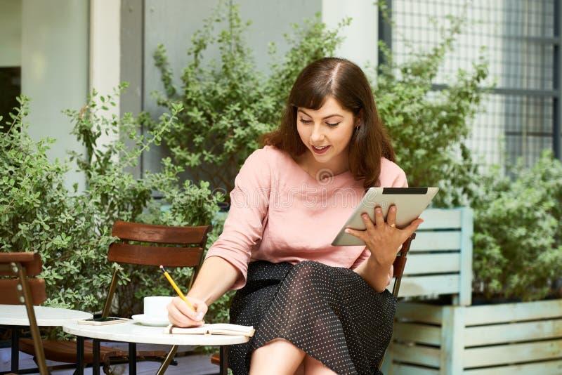 Pensamientos de la escritura de la mujer en planificador fotos de archivo libres de regalías